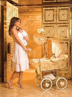 Donald Trump's wife holding their cute baby while holding a golden carriage in their Manhattan apartment that is completely lined with gold.