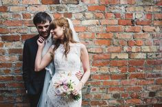 Bride & Groom photography against an urban exposed brick wall - A vintage inspired wedding in Northern Ireland with lace wedding dress, pink and green colour scheme and photographs by Connor McCullough wedding photographer