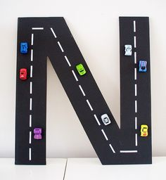 """N"" made from cardboard and little cars are just hot glued. Can put in a shadow box or hung just like this. So cute for a boys room!"