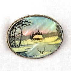 Russian Winter Scene Brooch - $52.99 Beautiful Winter! This luminescent mother of pearl brooch was hand painted in Russia. It features a magnificently detailed miniature painting of a classic Russian winter scene. It is made of a mother of pearl base that is nested into a German silver frame with a pin on the back. Each brooch is painted in the classical Fedoskino style. Fedoskino is the famous Russian school of miniature painting. #russia #russian #jewelry #winter #brooch
