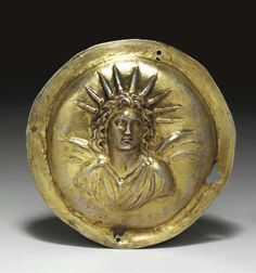 A GREEK GILT SILVER ROUNDEL WITH ALEXANDER-HELIOS   Hellenistic Period, Circa Late 4th Century B.C.   The miniature shield of Argive type hammered and decorated in repousseé with a bust of Alexander-Helios, the divinized conqueror depicted wearing a chiton pinned on each shoulder, his long curling locks framing his face, with characteristic anastole, some tendrils falling to his shoulders, his head surmounted by nine rays, designating his attribution as the sun god,