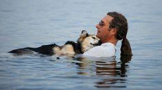 John Unger and his dog, Schoep, wade in Lake Superior. (Hannah Stonehouse Hudson/StonehousePhoto.com)