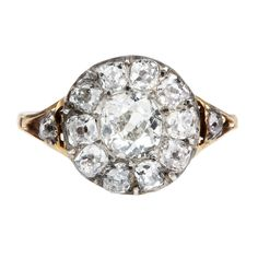 Mid 19th Century diamond ring. 11 old mine cut diamond stones set in a cluster pattern with 2 diamonds on either side. Diamonds are set in silver on gold. English in origin, circa 1850.   Size 7.75 , can be resized.