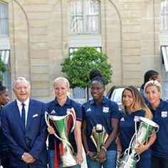 Lyon's Womens Football team pose with the UEFA Champions League trophy after their win