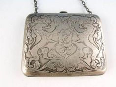 "An antique sterling silver "" card holder"" on a chain with a silver latch most likely used as a dance card carrier for formal social affairs."