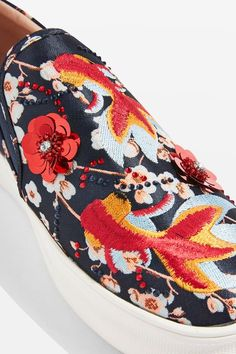 These fabulous embellished trainers are almost too good to wear. This easy slip-on style is adorned with a beautiful goldfish and floral motif - what a masterpiece! Complete with a cushioned ankle and elastic in the sides, it boasts a thick white platform for a little bit of height.