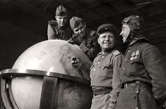 Soviet soldiers pose with 'Hitler's Globe'. Berlin, Germany, 1945.