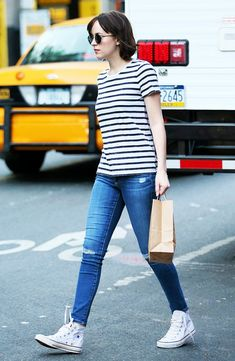 Dakota Johnson in a striped t-shirt, distressed skinny jeans, white Converse high-top sneakers, and round sunglasses