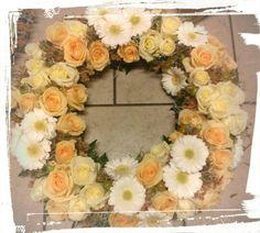 Rundbunden krans fyllt med krem og fersken roser,hvite germini, nyper,og strå -design ingunngrimsby