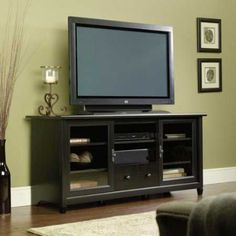The large center storage and glass paned side storage areas are each enhanced with an adjustable shelf for versatility. In addition, the center space is complete with a centered hole for cord management in the back. 52 inches Wide, 15.75 inches Deep, and 24 inches High, Mission Oak Finish, Center cord management, Holds up to a