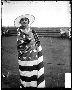 Portrait of Miss Miriam Mooney, a singer from Tennessee, wrapped in an American flag, standing near a low chain barricade at Grant Park in the Loop community area of Chicago, Illinois, c. 1917. Photograph from the Chicago Daily News. DN-0068632 #chicago #history #holiday #july4 #flag #american