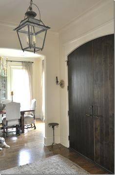 The front door is dark brown planked wood with small sconces flanking it.   Above is the lantern from Chateau Domingue.