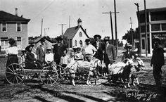 """This is an interesting photograph of Las Vegas. Does anyone know what might be going on here? The man in the cart might have dwarfism, and one goat is covered with a banner, where the last word is """"Pictures"""". Are these locals? A traveling circus or promoter?Edit 2/6:Apparently, goat carts were a thing, like sitting on a moon portraits, but less common. There were a number of traveling photographers between 1900 to 1920 who used goat carts as photo props to attract customers.For ..."""