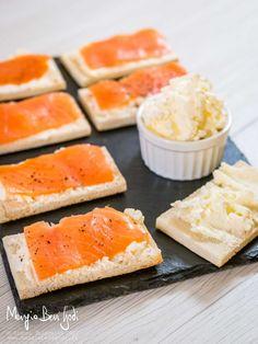 Crostini con salmone serviti su piatto di ardesia insieme a una ciotola di burro montato