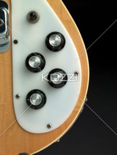 cropped image of volumes knobs of a guitar. - Close-up cropped shot of volumes knobs of electric guitar against dark background.