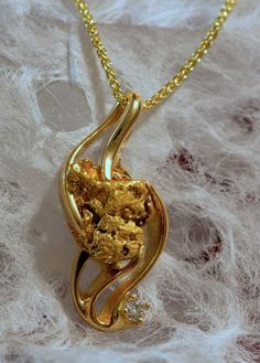 Elegant 14Kt yellow gold pendant set with a natural Alaskan gold nugget and a diamond.