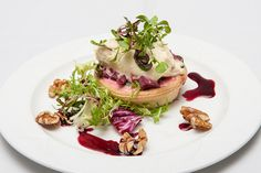 Beetroot & spinach tart resting on a walnut & rocket salad & topped with horseradish cream