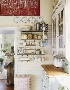 Shelves (made out of old shabby wood & wrought iron hardware?) on the wall with hooks underneath for saucers etc. Storage in kitchen