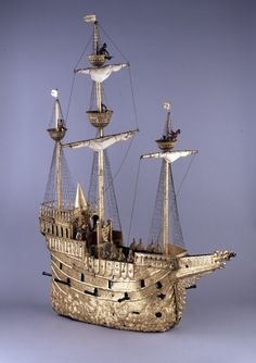 An automated clock in the form of a 'nef', or galleon, made by Hans Schlottheim. There was a great fascination for automated machines at the end of the sixteenth century, particularly at the courts of Rudolf II in Prague and Süleyman 'the Magnificent' in Constantinople. Hans Schlottheim of Augsburg (1545-1625) was one of the most famous makers of these machines. This gilt-copper and steel automaton was designed to trundle along a grand table to announce a banquet. It takes the form of a nef…