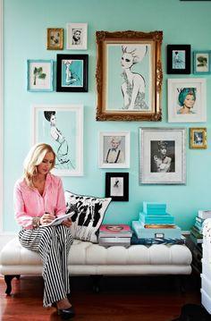 Beautifully mixed-matched framed fashion art against a bright aqua wall.