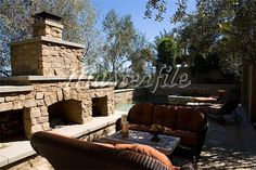 Outdoor sitting area with sofas near stone fireplace Stock Photos