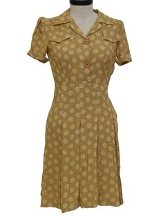 40s -Bullocks of Los Angeles Sunkist Fashions- Womens tan and cream swirl print rayon blend mid length designer day dress. Notched fold over loop collar for modesty when required or left open for v-neckline with that draws the eye down two oversized bake lite button placket facade. Shirt dress styling with short light padded pre-cuffed cap sleeves, two flap top pocket facades on bodice, double darted bust and empire waistline with drop seams that open to tight pinch pleated panels down…
