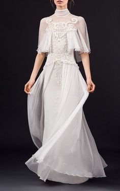 This **Temperley London** Rowena is a demure, feminine dress with a Pre-Raphaeite feel that features a high neck sash, crinkle silk chiffon tiers on emboridered tulle, delicate embroidered chiffon flowers accented by fine ruffles, and mother of pearl and Swarovski embellishments.