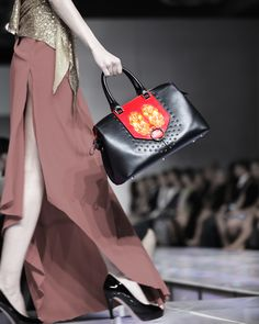 A model is holding a Bellorita black and red hand tooled and hand painted PX leather satchel on her hand.