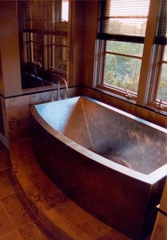 And this copper bathtub has a beautiful warm patina to it. If you look closely, you can see that the bottom is curved up under the knee area. A nice touch that would keep you from sliding down in the tub when you lean back