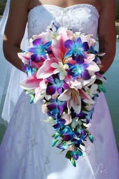pink lilies and blue orchid wedding bouquet. beautiful colors.