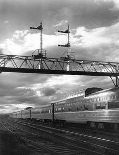 Northern Pacific's North Coast Limited streamlined passenger train passing under a signal bridge at sunset in western Montana, circa 1960s. Following World War II, many western railroads promoted their scenic beauty with vista-dome cars on their premier passenger trains.