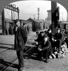 Clyde, Queen's Dock, Workers on the North Quay A group of dockworkers is pictured on the North Quay of Queen's Dock in 1908, waiting for an assignment. It cannot have been very comfortable sitting on a pile of granite setts. Apart from pipe smoking and the occasional rich conversation there would not have been much to occupy the workers until a vessel needed service.