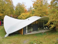 "The 1968 house's shape—a rounded triangle topped with a sweeping concrete roofline that suggests a helmet as it rises above huge banks of windows—lends itself totally to Kukkapuro's philosophy. ""It is a structure in waiting, prone to change as the landscape around it—not yet a form, rather a possibility,"" he says. ""It changes in harmony with the seasons and the moods of its inhabitants.""  Photo by: Johannes Romppanen"