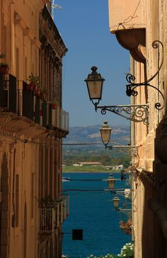 A narrow street with a view of the sea, Siracuse, Sicily, Italy