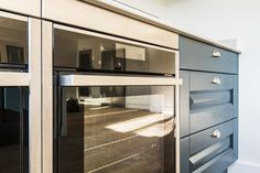 Two slide and hide Neff pyrolytic ovens were installed in this mackintosh kitchen - perfect for entertaining! #makintoshkitchen #kitchendesign #cooking #neff #oven #selfcleaningoven #kitchendesigner #kitchen #bluekitchen