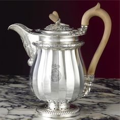 A Royal George IV silver coffee jug, Philip Rundell for Rundell, Bridge and Rundell, London, 1821 the fluted pear-shaped body engraved with a Royal cypher on each sude under Royal Ducal coronet, berried laurel border, pierced foot and twin acorn finial height 8 1/2in.