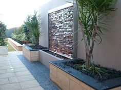 Water feature and landscaping along fence