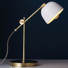 A highly adjustable raw brass task lamp is topped with an ultra-thin slip cast porcelain lamp shade covered in a white crawl glaze for a compelling and unique surface texture. Featuring a 90 degree sw