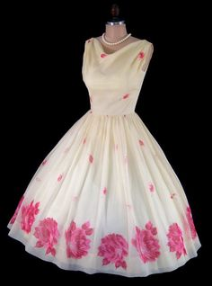 This stunning 1950s off-white silk chiffon party or prom dress features a beautifully fitted bodice, draped neckline, nipped waist and