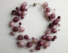 Matt schimmernde Perlen in Beerentönen umschmeicheln Hals und Dekolleté. Obwohl am Hals anliegend, scheinen die Perlen zu schweben. Diese Ketten si...