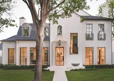 Stunning 2-story white stucco modern home accented with a gray shingled roof boasts a long concrete pathway…
