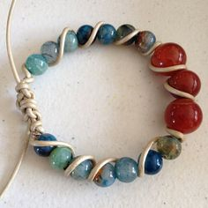 A large orb of red orange surrounded by smaller orbs of blue, brown and green dragon;s vein agate, with a twisted vine of pale blond leather cord. adjustable with a shambala style closure.  Custom Available  Choice of stone and leather -brown, black or blond $45-60 depending on stone selection....