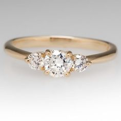 This lovely three stone diamond ring features round brilliant diamonds in an elegant low profile design. The center diamond weighs .36 carats and the accent diamonds weight .10 carats each. The three diamonds all total .56 carats and grade G-H in color and I1 in clarity. The ring is crafted of 14k yellow gold and is currently a size 6.25. We offer complimentary resizing to fit. COMPOSITION 14k Yellow Gold PRIMARY STONE Round Brilliant Center Diamond MEASUREMENTS .36 Carat - 4.56-4.57mm X…