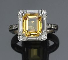 A yellow sapphire and diamond ring centering a radiant-cut yellow sapphire, weighing approximately: 3.00 carats; mounted in eighteen karat white gold