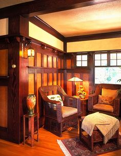 Sitting room/den with wicker furniture in the Arts  Crafts- Mission style. Love the wainscoting, plate rail and pop of orange.