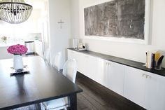 Install basic Ikea kitchen cabinets a bit lower, add a slab of stained wood on top, and you've got a custom sideboard. Back wall of living room?