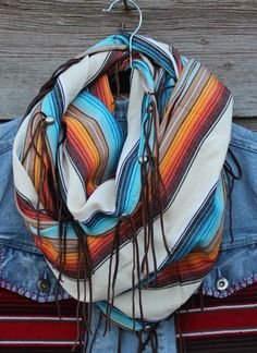 White Linen Multi-Colored Infinty Scarf with Fringe. Hand woven textiles from Boot Rugs with pressed studs and leather fringe detail. Can be worn as wrap, serape, or infinity scarf.