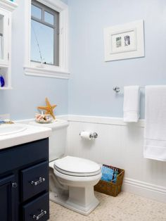 Soothing blue tones bring a clean, crisp look to this coastal-themed bathroom. Designer Erica Islas suggests painting your existing cabinets navy blue and replacing hardware with glass knobs and pulls. To add texture, paint beadboard stark white to wainscot the bottom half of the walls and paint the upper half a soothing blue color for a serene feel. Decorate with beach-inspired accessories and framed images of the beach.