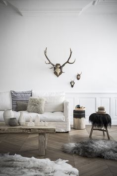 Modern rustic living room, white paneling, antlers, white sofa, textures, wooden table