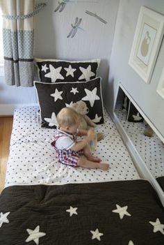 matelas lit bébé à même le sol, blanc à points noirs, couverture de lit, oreillers noirs à étoiles blanches, mur couleur blanche, bébé, jouet ourson
